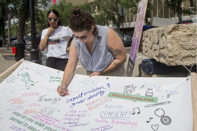 People writing on a banner why sex-ed is important