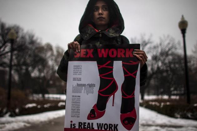 A woman (requested to withhold her name) holds a sign during a rally at Allan Gardens park to support Toronto sex workers and their rights in Toronto, Friday December 20, 2013. (Mark Blinch / THE CANADIAN PRESS)