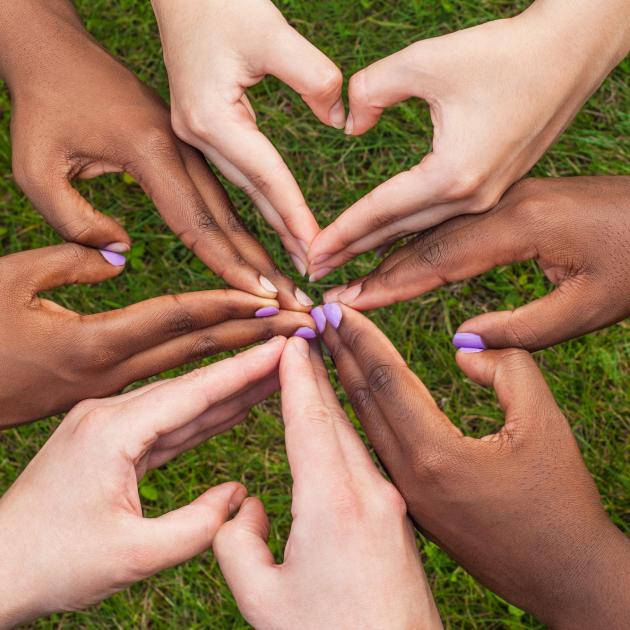 Diverse hands forming hearts together
