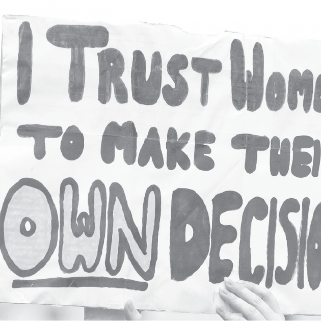 Hand holding rally sign that reads: I trust women to make their own decisions