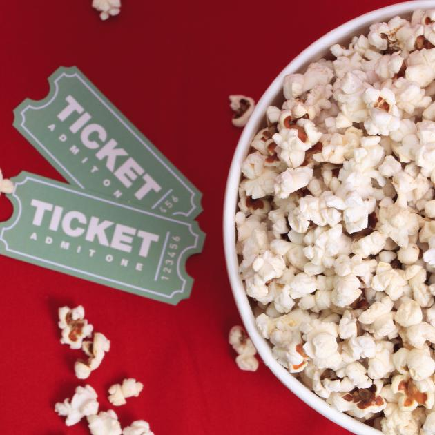 Two movie tickets beside a bucket of popcorn